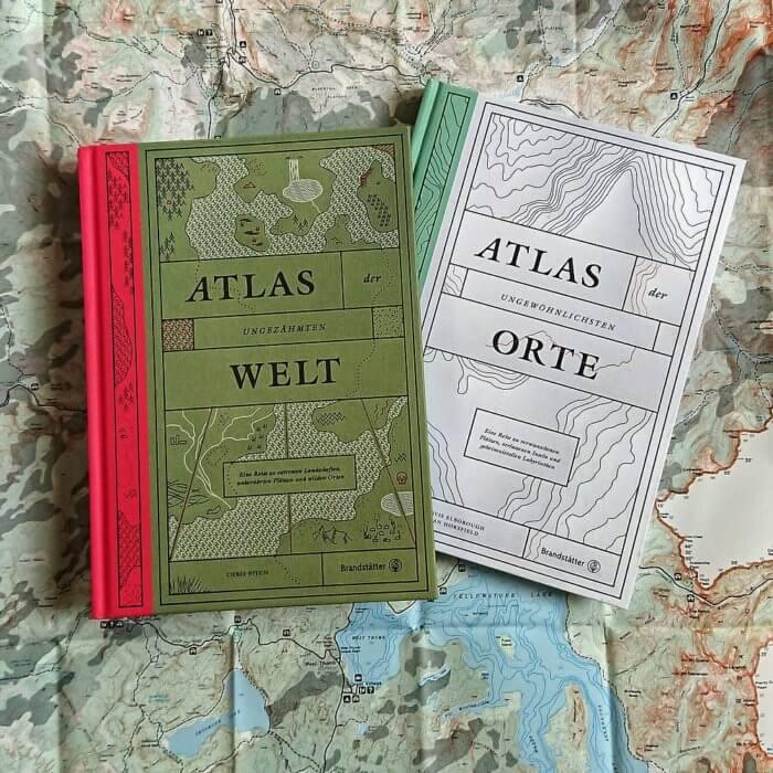Atlas der ungezähmten Welt & Atlas der ungewöhnlichsten Orte. Brandstätter Verlag. Beide Bücher liegen auf einer Landkarte.