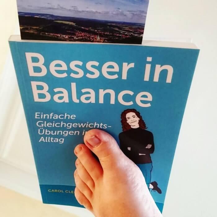 Carol Clements: Besser in Balance Einfache Gleichgewichtsübungen im Alltag | Gesund und fit in jedem Alter | für mehr Beweglichkeit und Wohlbefinden | Balance üben, Stürze vermeiden und aktiv bleiben!Besser in Balance Einfache Gleichgewichtsübungen im Alltag | Gesund und fit in jedem Alter | für mehr Beweglichkeit und Wohlbefinden | Balance üben, Stürze vermeiden und aktiv bleiben! Das Buch balanciert auf einem gen Decke ausgestrecktem Fuß.