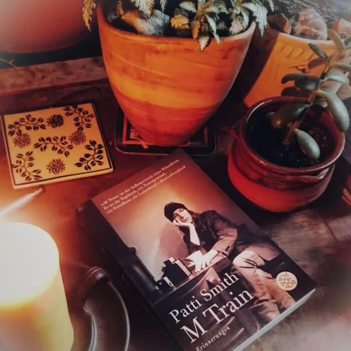 Die Taschenbuchausgabe von m-Train von Patti Smith im Kerzenlicht.