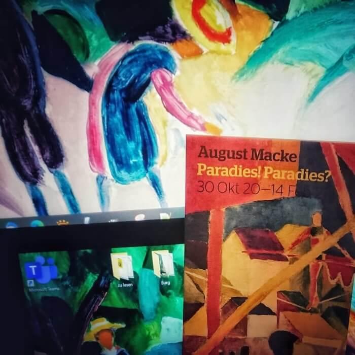 August MAcke. Paradies! Paradies? Flyer zur Ausstellung im Museum Wiesbaden vor meinem Computer-Bildschirm, auf dem ein Bild von August Macke als Bildschirmhintergrund zu sehen ist.
