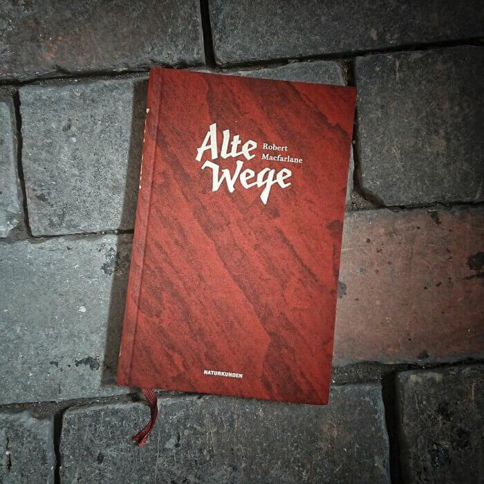 Alte Wege von Robert Macfarlane. Das Buch liegt auf einem Weg aus alten Ziegelsteinen.