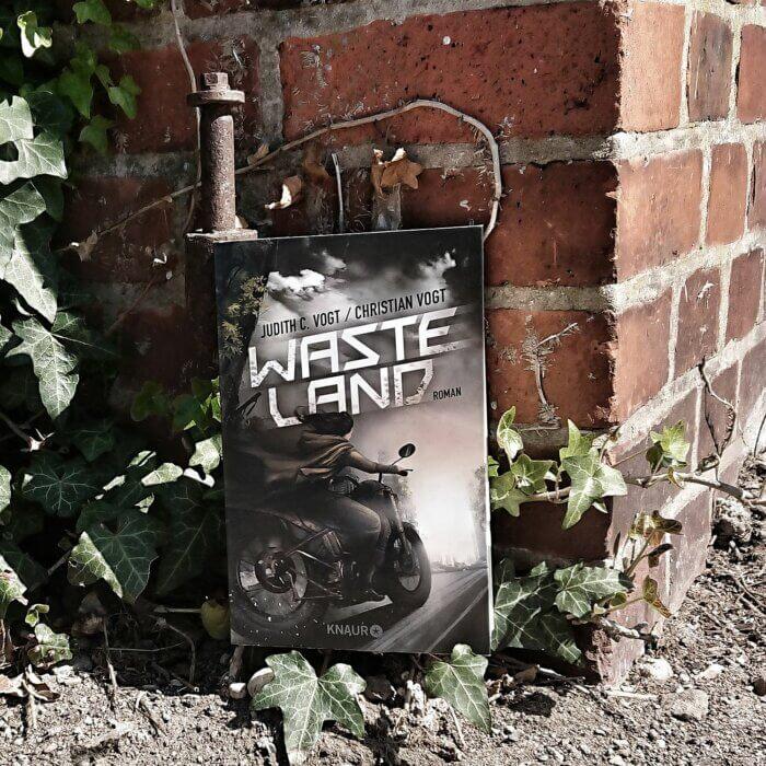 Wasteland. Buch vor einer Wand mit Efeu.