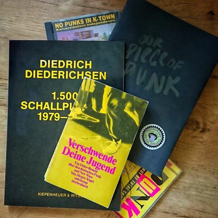 """Das Buch """"Verschwende deine Jugend - Ein Doku-Roman über den deutschen Punk und New Wave"""" liegt auf einem unordentlichen Buchstapel mit weiteren Büchern über Punk"""