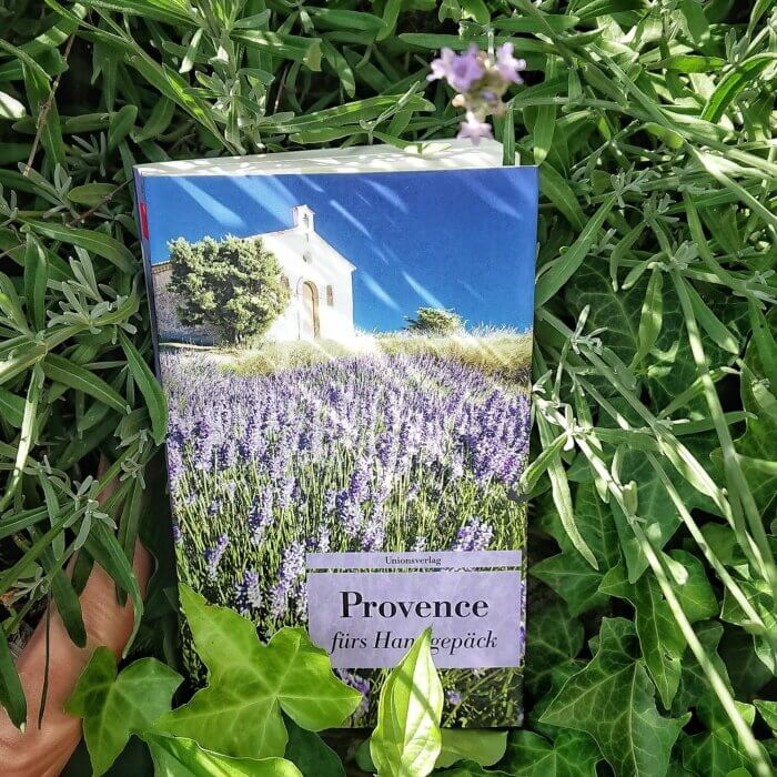 """Taschenbuch """"Provence fürs Handgepäck"""". Buch liegt unter einem Lavendelbusch"""
