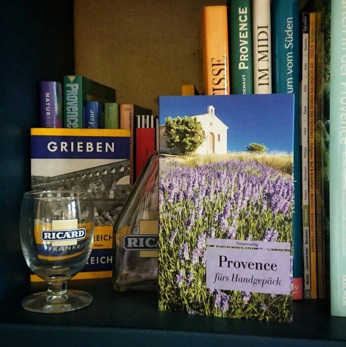 Provence fürs Handgepäck. Das Taschenbuch steht in einem Buchregal voller Bücher über die Provence, daneben ein Pastis Glas