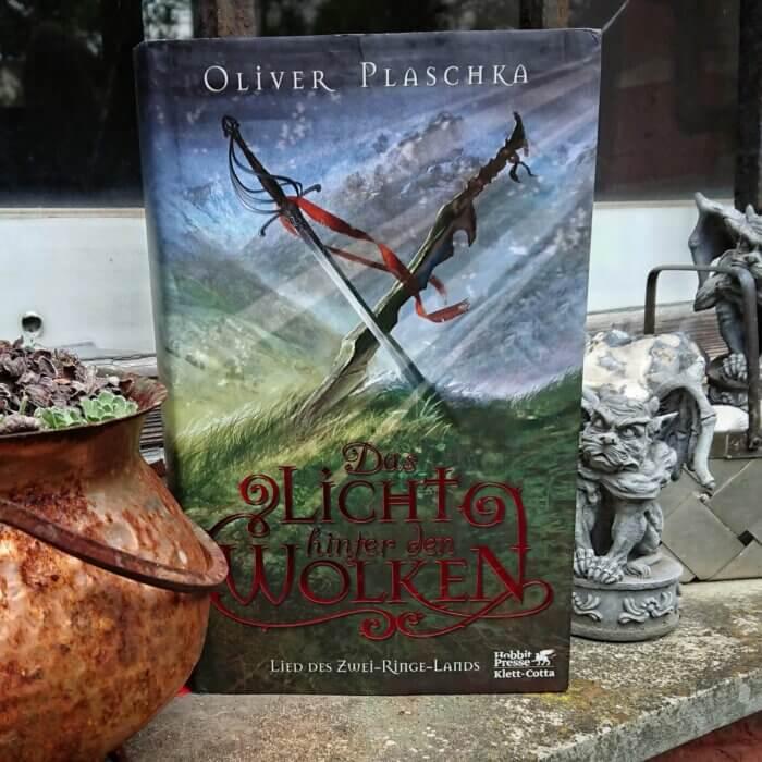 Oliver Plaschka - Das Licht hinter den Wolken. Fantasy Roman. Aufgenommen im Garten neben einem Deko-Gargoyle.